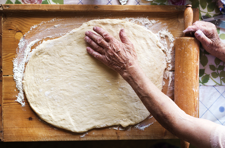 woman baking: Senior woman baking pies in her home kitchen. Rolling dough using rolling pin.