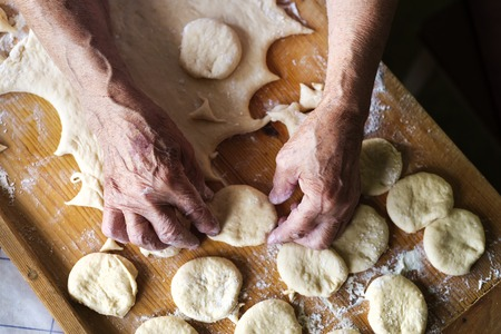 woman hands up: Senior woman baking pies in her home kitchen. Cutting out circles from raw dough.