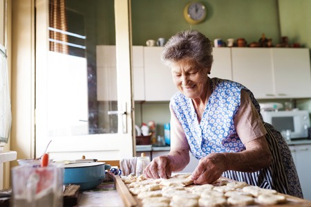 bread: Senior woman baking pies in her home kitchen. Cutting out circles from raw dough.