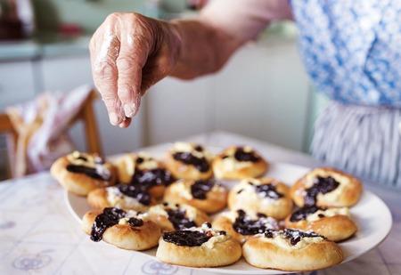 Anziani torte donna di cottura nella sua cucina casa. Cospargere panini appena sfornati con zucchero a velo.