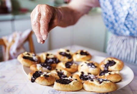 Senior woman baking pies in her home kitchen. Sprinkling freshly baked buns with powdered sugar. Stock Photo