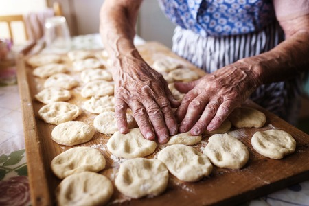 woman baking: Senior woman baking pies in her home kitchen. Cutting out circles from raw dough.
