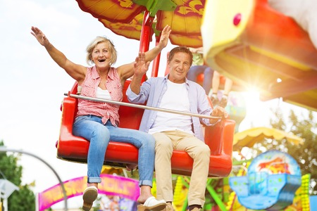 tercera edad: Pares mayores que se divierten en el parque de atracciones