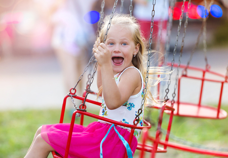chain swing ride: Cute little girl having fun at fun fair