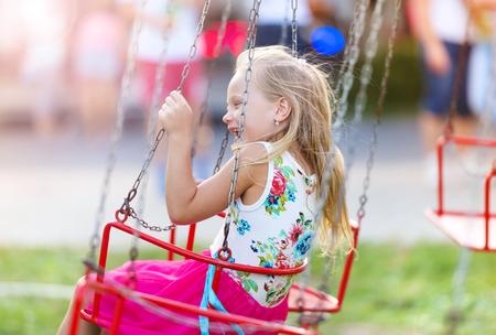 chain swing ride: Cute little girl having fun at fun fair