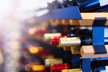 Various wine bottles in row on wooden shelf.