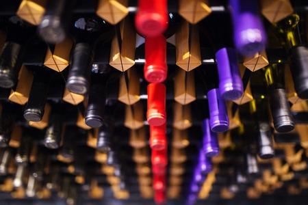 tomando alcohol: Varias botellas de vino en fila en el estante de madera.