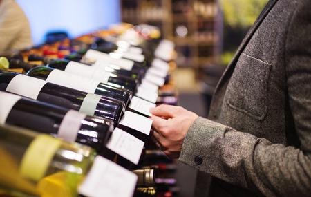 Unrecognizable young man in a wine shop choosing a wine Archivio Fotografico