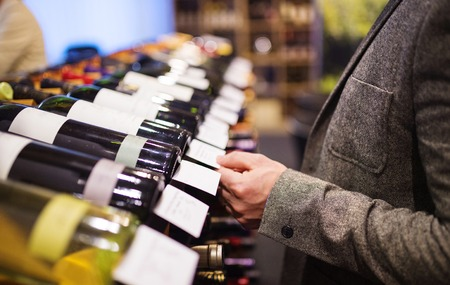 grocery shelves: Unrecognizable young man in a wine shop choosing a wine Stock Photo