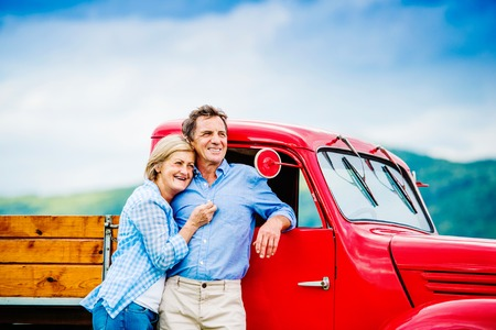 active retirement: Senior couple standing by their vintage red car