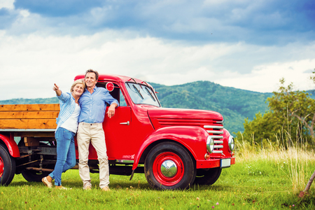 vintage car: Senior couple standing by their vintage red car