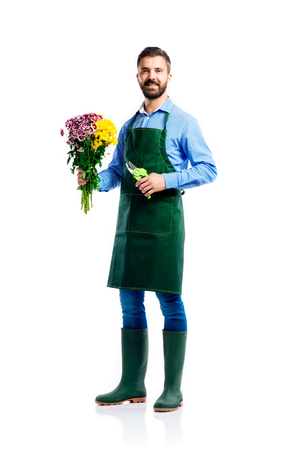 young worker: Young handsome gardener in green apron. Studio shot on white background