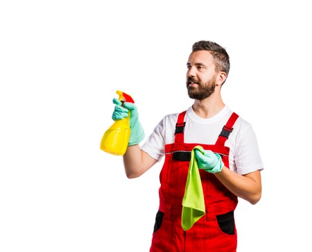 work gloves: Young handsome cleaner in red overalls. Studio shot on white background