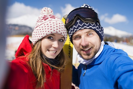 two men: Young couple skiing outside in sunny winter mountains Stock Photo