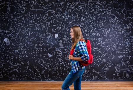 estudiando: Hermosa chica escuela joven delante de gran pizarra. Estudio dispar� sobre fondo negro.