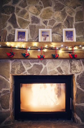burning fireplace: Fireplace with christmas decorations and a light chain