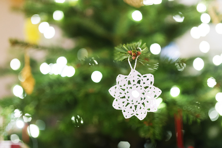 christmas decorations: Close up of a white crocheted decoration hang on Christmas tree Stock Photo