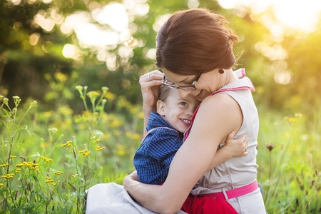 human arm: Happy young mother holding her son outside in summer nature