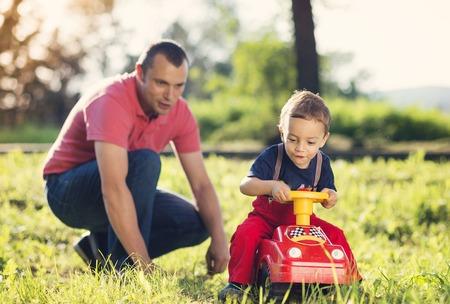 carritos de juguete: Feliz padre jugando con su hijo al aire libre en la naturaleza del verano Foto de archivo