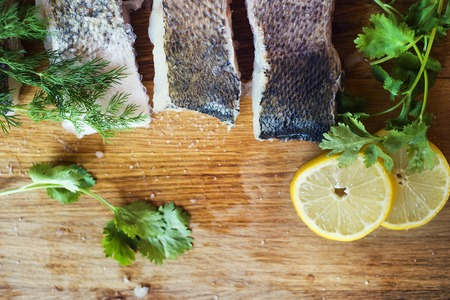 zander: Raw zander fish fillets with lemon slices and herbs on a wooden cutting board.