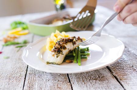 judia verde: El hombre que sirve filetes de pescado lucioperca en un plato