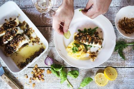comida: El hombre que sirve filetes de pescado lucioperca en un plato