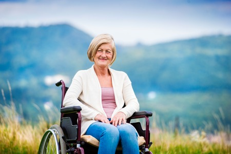active lifestyle: Senior woman in wheelchair outside in nature
