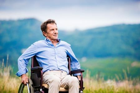 silla de ruedas: Hombre mayor en silla de ruedas fuera en la naturaleza