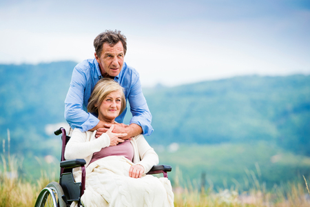 woman white shirt: Senior man with woman in wheelchair outside in nature Stock Photo