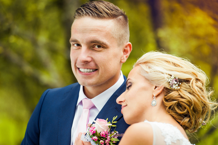 smile close up: Beautiful young wedding couple outside in nature Stock Photo
