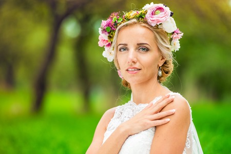 celebration event: Beautiful young bride with flower wreath outside in nature