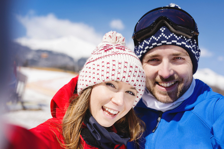 couple nature: Young couple skiing outside in sunny winter mountains Stock Photo