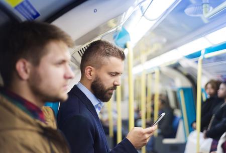 multitud: Apuesto hombre de negocios joven con el tel�fono inteligente en el metro Foto de archivo
