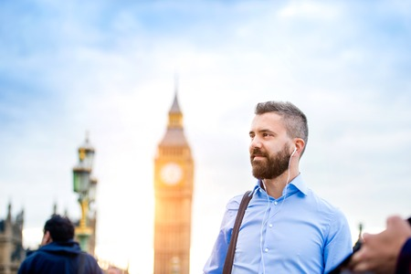 british weather: Handsome young man in blue shirt on Westminster bridge