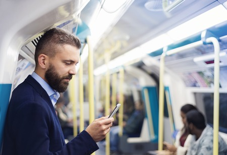 station: Young handsome businessman with smartphone in subway Stock Photo
