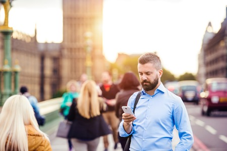 westminster bridge: Handsome young man with smart phone on Westminster Bridge