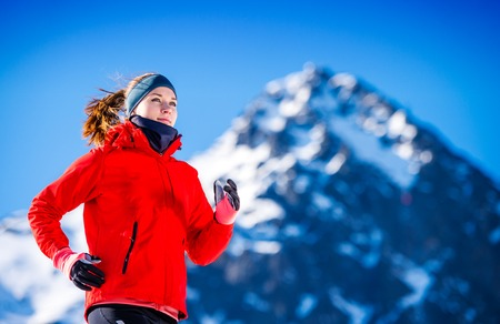 and activities: Young woman jogging outside in sunny winter mountains Stock Photo