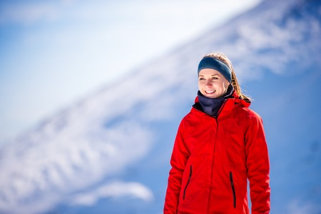 crosscountry: Young woman jogging outside in sunny winter mountains Stock Photo
