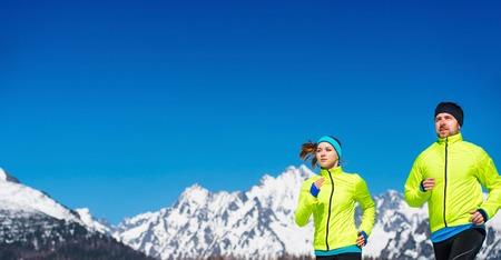 hombre deportista: Pareja joven que activa al aire libre en las monta�as soleados de invierno