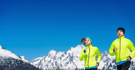 couple winter: Young couple jogging outside in sunny winter mountains