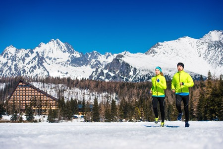 crosscountry: Young couple jogging outside in sunny winter mountains
