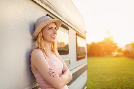 camper trailer: Beautiful young woman outside the camper van on a summer day