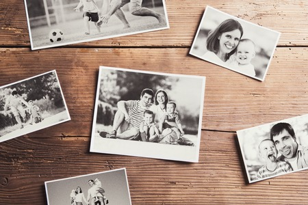 Black and white family photos laid on a table. Studio shot on wooden background. Stock Photo - 46808771