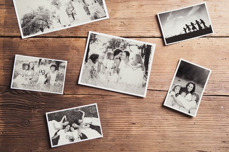 history background: Black and white family photos laid on a table. Studio shot on wooden background.