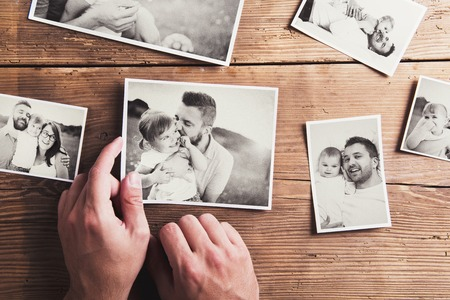 memories: Black and white family photos laid on a table. Studio shot on wooden background.