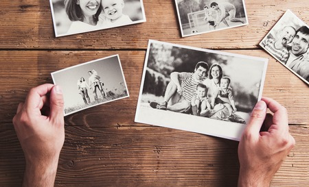 Photos de famille en noir et blanc posé sur une table. Tourné en studio sur fond de bois.