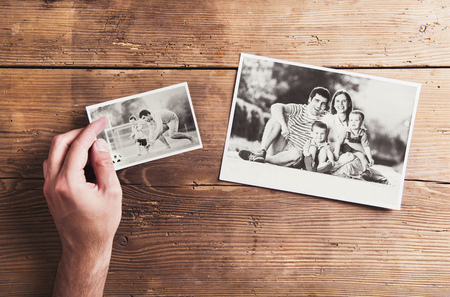 dad son: Black and white family photos laid on a table. Studio shot on wooden background.