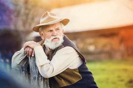 organic farm: Senior man standing outside at the wooden fence Stock Photo