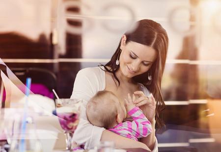 Hermosa joven madre que amamanta a su pequeño bebé