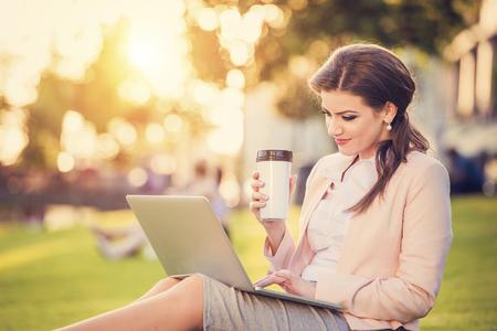 almuerzo: Hermosa mujer de negocios joven sentado en un parque durante una pausa para el almuerzo.